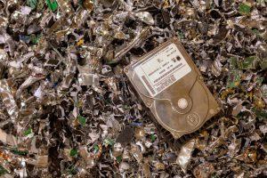 A hard drive waiting destruction resting on a pile of shredded hard drives